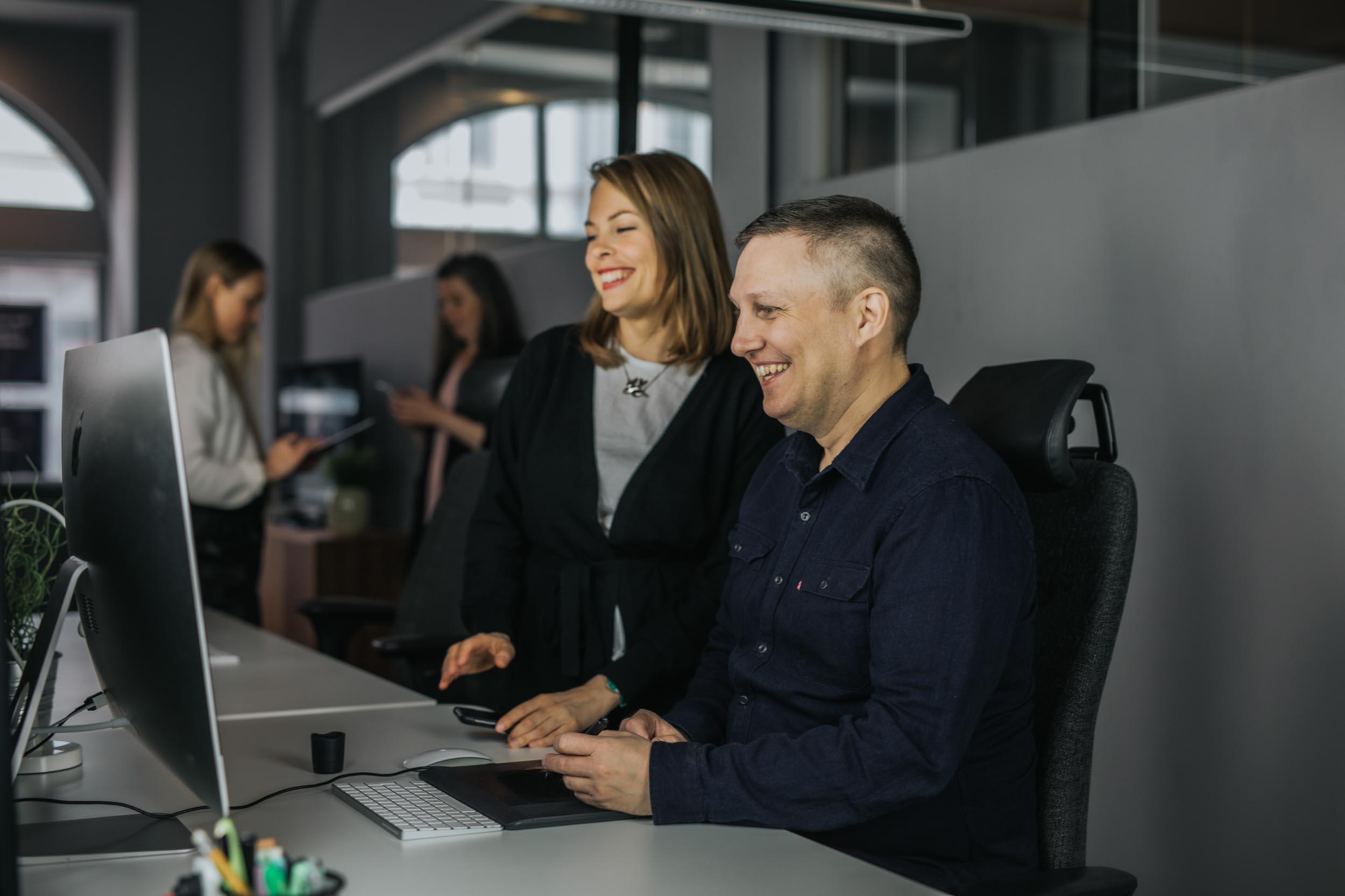 Malin och Simon på Bishop Media jobbar vid en iMac